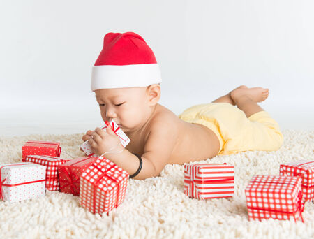 Asian baby boy with santa hat playing with Christmas present on floor. photo