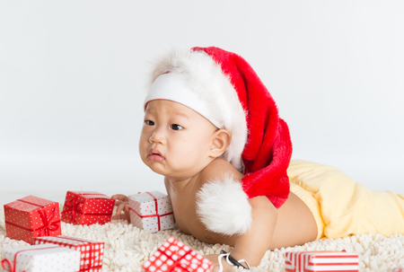 Asian santa hat baby boy with Christmas gift on floor. photo