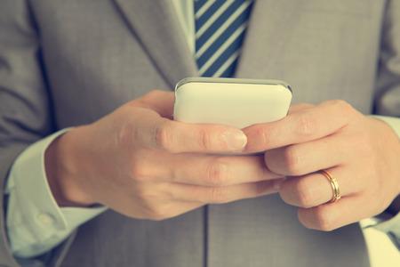 Close-up businessman hand using smart phone in retro tone. photo