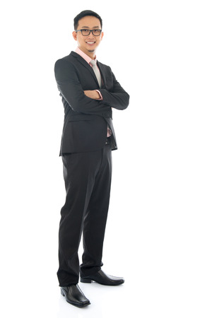 Full length confident southeast Asian business man crossed arms standing isolated on white background. Stock Photo