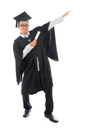 exaggerate: Full length pan Asian university student in graduation gown, standing isolated on white background.