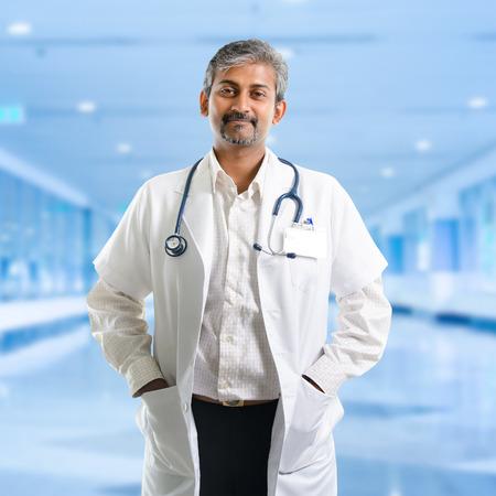 Mature Indian male medical doctor standing inside hospital. Handsome Indian model portrait.