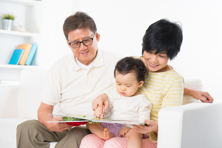 Asian family reading book sitting on sofa indoor, grandparents and grandchild living lifestyle at home. photo