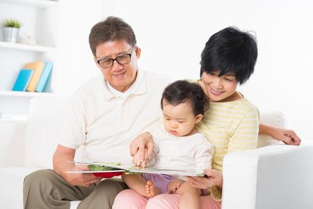 Libro de lectura de la familia asiática que se sienta en el sofá cubierta, abuelos y nietos de estilo de vida que viven en casa.