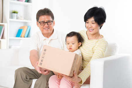 Asian family received an express courier parcel and open it at home, grandparents and grandchild living lifestyle indoor. Stock Photo