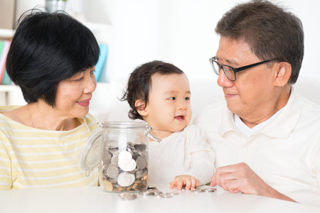 Asian family saving money indoor, financial concept, grandparents and grandchild living lifestyle at home.