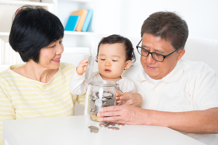 Asian family saving money indoor, grandparents and grandchild living lifestyle at home, financial concept. photo
