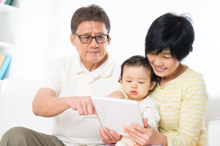 people   lifestyle: Asian family using digital tablet computer, grandparents and grandchild living lifestyle at home.