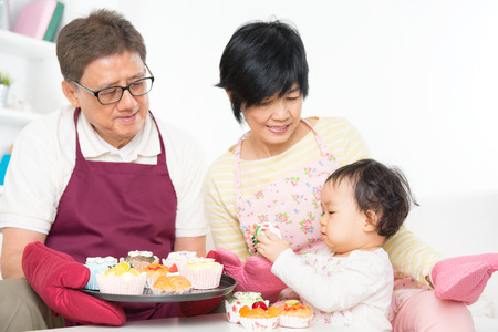 multi family house: Asian family baking cake, grandparents and grandchild indoor living lifestyle at home.