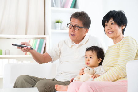 grandkids: Asian family watching movie together, grandparents and grandchild indoor living lifestyle at home.