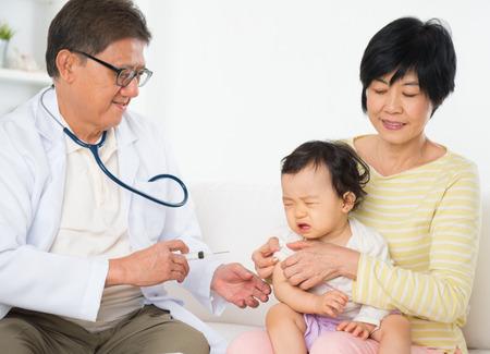 niño llorando: Vacunas médico de familia o la inyección a la niña. Pediatra y paciente. Foto de archivo