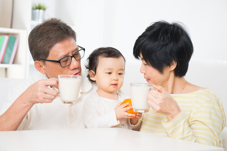 three generation: Asian family drinking milk, grandparents and grandchild indoor living lifestyle at home.