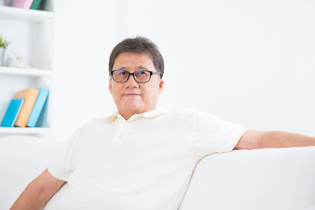 Portrait of mature Asian man smiling, sitting on sofa at home, senior retiree indoors living lifestyle.