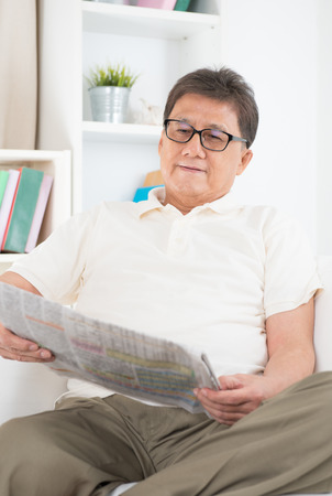 Portrait of mature Asian man reading on newspaper, sitting on sofa at home, senior retiree indoors living lifestyle. Stock Photo