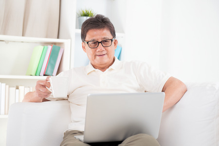 Portrait of mature Asian man using computer laptop, enjoying cup of coffee in morning, sitting on sofa at home, senior retiree indoors living lifestyle. Stock Photo
