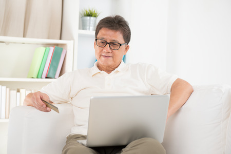 Portrait of mature Asian man using computer doing online shopping with credit card, sitting on sofa at home, senior retiree indoors living lifestyle. photo