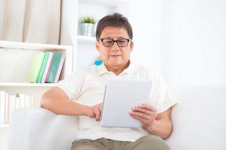Portrait of mature Asian man using tablet pc, sitting on sofa at home, senior retiree indoors living lifestyle. photo