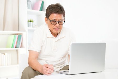 Portrait of mature Asian man using computer laptop and writing something on paper, sitting on sofa at home, senior retiree indoors living lifestyle. photo