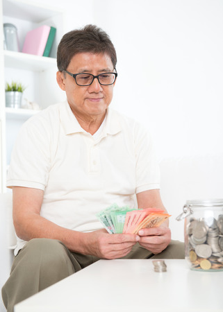 Portrait of mature Asian man counting on his savings, sitting on sofa at home, senior retiree indoors living lifestyle.