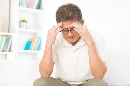 Portret van de volwassen Aziatische man met hoofdpijn, zittend op de bank thuis, senior gepensioneerde binnenshuis levende levensstijl.