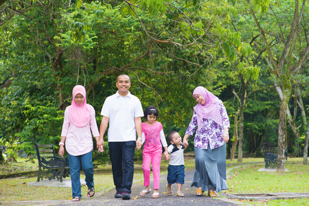 malay: Asian family holding hands walking together on garden path. Happy Southeast Asian outdoor lifestyle.