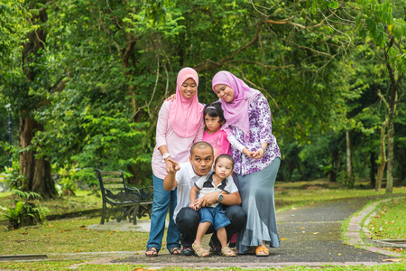 Happy Southeast Asian family outdoor lifestyle at nature green park. photo