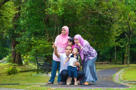 malay boy: Happy Southeast Asian family outdoor lifestyle at nature green park, pointing and looking away. Stock Photo