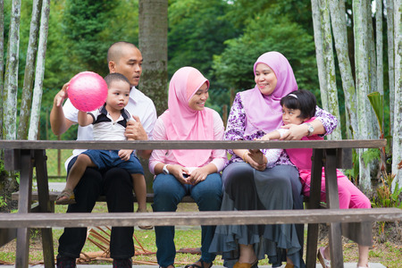 Happy Southeast Asian family sitting at garden bench chatting with each other, outdoor lifestyle at nature green park. photo