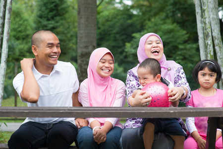 malay boy: Happy Southeast Asian family sitting at garden bench laughing together, outdoor lifestyle at nature green park.
