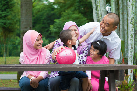 malay boy: Happy Southeast Asian family sitting at garden bench having fun, outdoor lifestyle at nature green park.