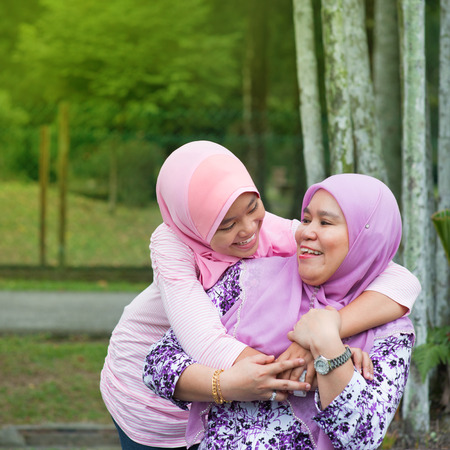 Happy Southeast Asian Muslim mother and daughter at outdoor park, family lifestyle. photo