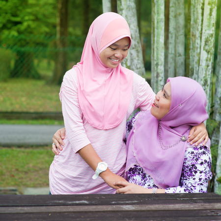 mother and teen daughter: Southeast Asian Muslim mother and daughter at outdoor park, happy family lifestyle. Stock Photo