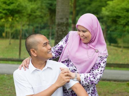 aged: Sud-Est asiatico coppia musulmana al parco esterno, felice stile di vita familiare.