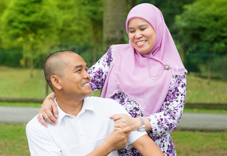 Middle aged Southeast Asian Muslim couple at outdoor park, happy family lifestyle.
