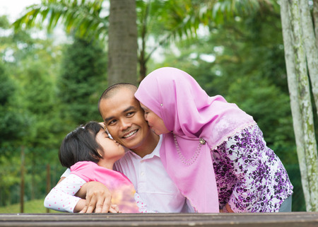 Happy Southeast Asian Muslim family, kissing on father face, outdoor lifestyle at nature green park.
