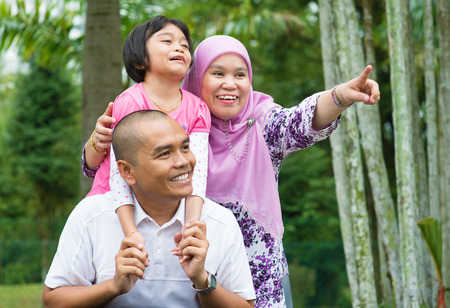 Happy Southeast Asian Muslim family pointing away, outdoor lifestyle at nature green park.