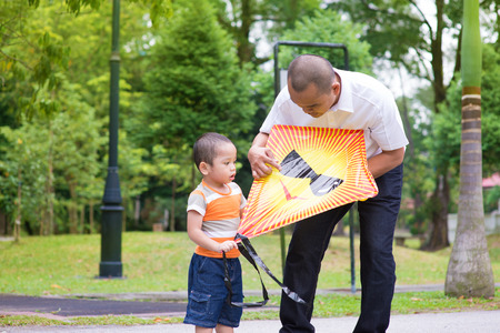 Father teaching son to fly a kite at outdoor garden park. Happy Southeast Asian family living lifestyle. photo