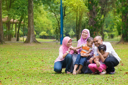 Happy family having fun at outdoor green lawn. Southeast Asian people living lifestyle. photo