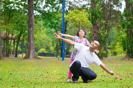 piggyback ride: Father and daughter playing at outdoor garden park. Happy Southeast Asian family living lifestyle.