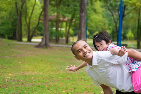 shoulder ride: Father and daughter playing piggyback at outdoor garden park. Happy Southeast Asian family living lifestyle. Stock Photo