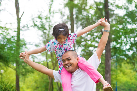 carry: Father and daughter playing piggy back at outdoor garden park. Happy Southeast Asian family living lifestyle.