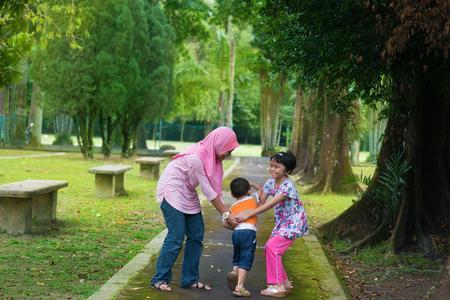 niños jugando en el parque: Niños jugando en el parque jardín al aire libre. Estilo de vida feliz de estar sudeste asiático de la familia.
