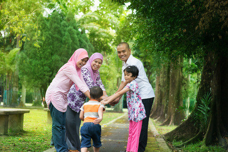 Happy family playing at outdoor garden park. Southeast Asian people living lifestyle.