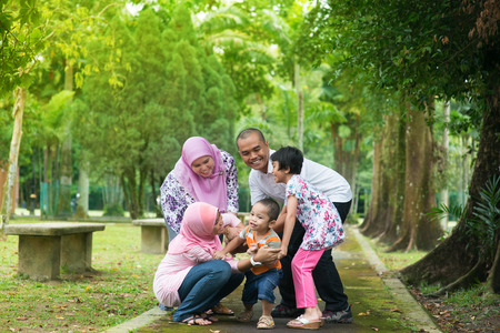 malay boy: Family playing at outdoor garden park. Happy Southeast Asian people living lifestyle.