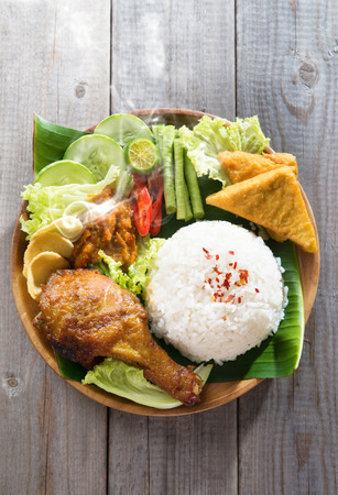 indonesian food: Popular Indonesian local food nasi ayam penyet, indonesian fried chicken rice with sambal belacan. Fresh hot with steam smoke. Stock Photo