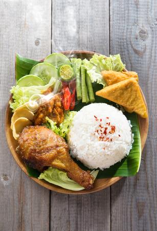malaysian food: Popular Indonesian local food nasi ayam penyet, indonesian fried chicken rice with sambal belacan. Fresh hot with steam smoke. Stock Photo