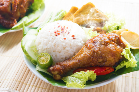 Popular Indonesian local food nasi ayam penyet, indonesian fried chicken rice with sambal belacan. Fresh hot with steam smoke. 免版税图像