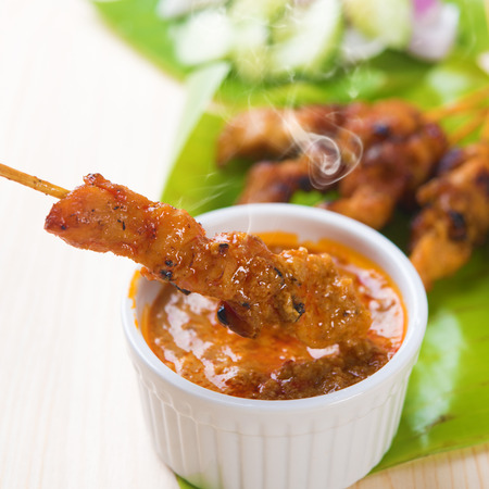 Delicious chicken sate or satay, skewered and grilled meat, served with peanut sauce. Fresh cooked with steamed and smoke. Hot and spicy Asian dish.