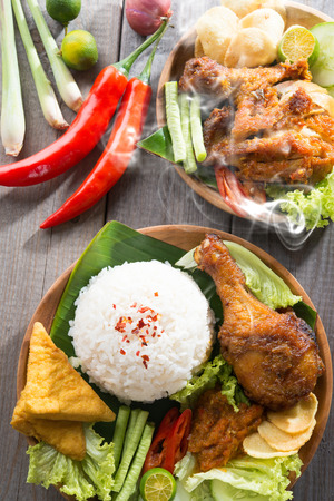 Popular delicious Indonesian local food nasi ayam penyet, indonesian fried chicken rice with sambal belacan. Fresh hot with steam smoke.