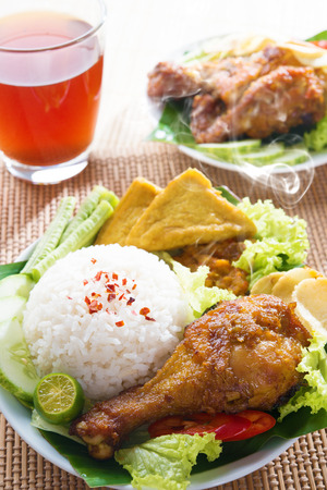 chicken rice: Popular Indonesian local food nasi ayam penyet, indonesian fried chicken rice. Fresh hot with steam smoke.